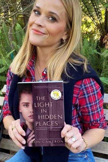 Reese Witherspoon holds up The Light in Hidden Places, which is now a part of her book collection. PHOTO FROM REESE WITHERSPOON FACEBOOK